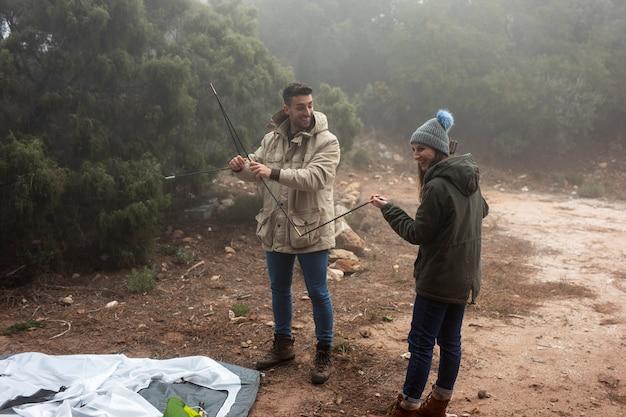 Persone a tutto campo che montano una tenda Foto Gratuite