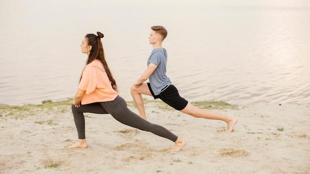 Persone a tutto campo che si esercitano sulla spiaggia Foto Gratuite