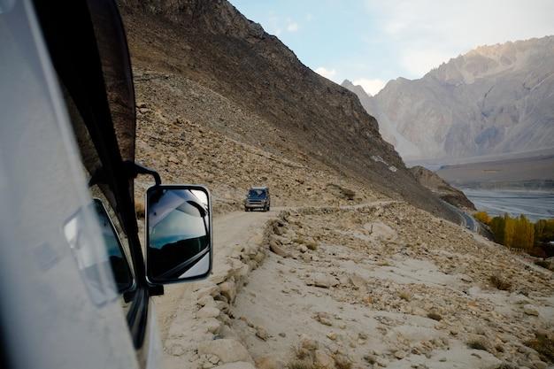 Persone alla guida di fuoristrada lungo la strada di montagna. Foto Premium