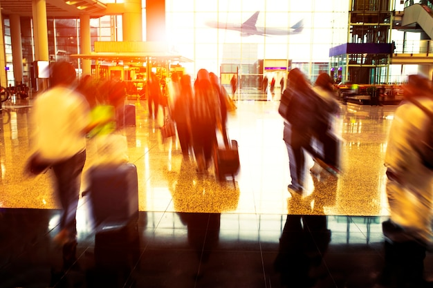 Persone con bagagli che viaggiano a piedi nel terminal dell'aeroporto Foto Premium