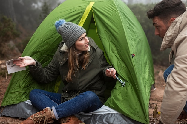 Persone con mappa e tenda a parlare Foto Gratuite