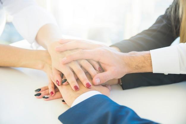 Persone di affari che si impilano mano sullo scrittorio bianco Foto Gratuite