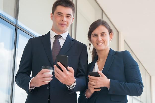 Persone di affari fiduciose allegre con gli smartphone Foto Gratuite