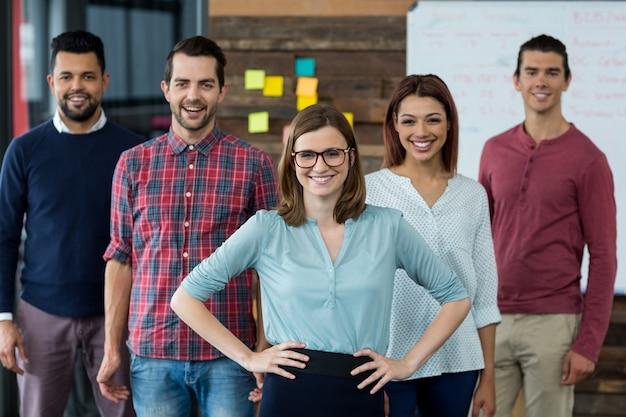 Persone di affari sorridenti che stanno nell'ufficio Foto Premium
