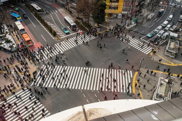 Persone e auto folla con attraversamento pedonale di vedute pedemontane intersezione attraversamento pedonale shibuya Foto Premium