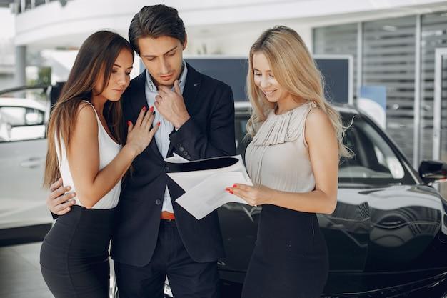Persone eleganti e alla moda in un salone di auto Foto Gratuite