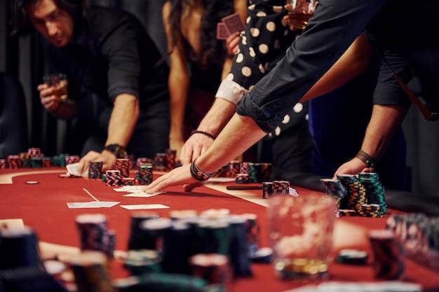 Persone in abiti eleganti in piedi e giocare a poker nel casinò insieme Foto Premium