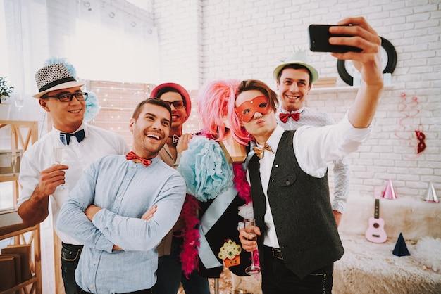 Persone in cravatte a farfalla prendendo selfie sul telefono alla festa. Foto Premium