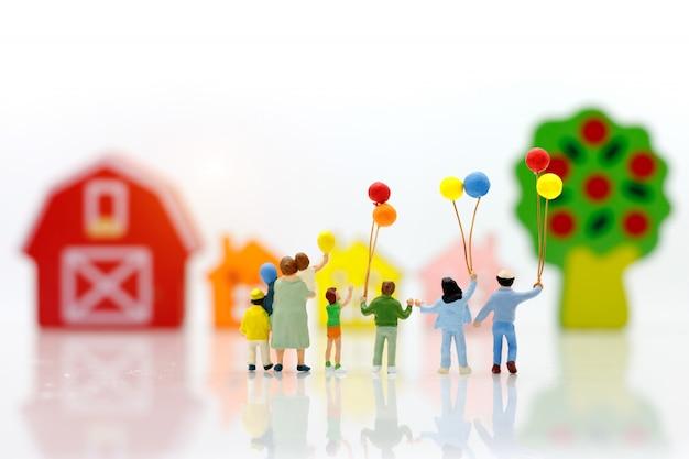 Persone in miniatura con palloncino azienda famiglia con case. Foto Premium