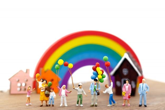 Persone in miniatura, famiglia e bambini si divertono con palloncini colorati. Foto Premium