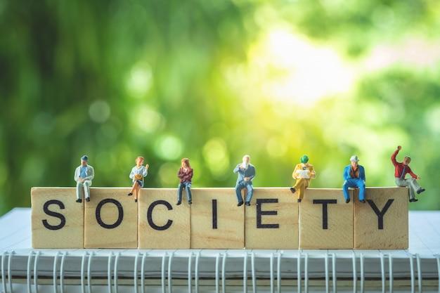 Persone in miniatura, gruppo di uomini d'affari seduti su blocchi di legno con la parola società. Foto Premium