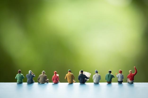 Persone in miniatura: gruppo di uomini d'affari seduti su un libro. Foto Premium