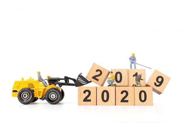 Persone in miniatura: il gruppo di lavoratori crea il blocco di legno numero 2020 Foto Premium