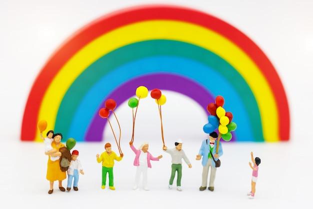 Persone in miniatura: la famiglia e i bambini si divertono con il palloncino colorato. Foto Premium