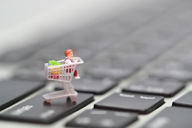 Persone in miniatura: la stampa di un acquirente entra nella tastiera del computer come pagamento online da casa Foto Premium
