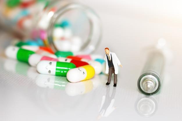 Persone in miniatura: medico con droga e siringa. concetto di assistenza sanitaria. Foto Premium