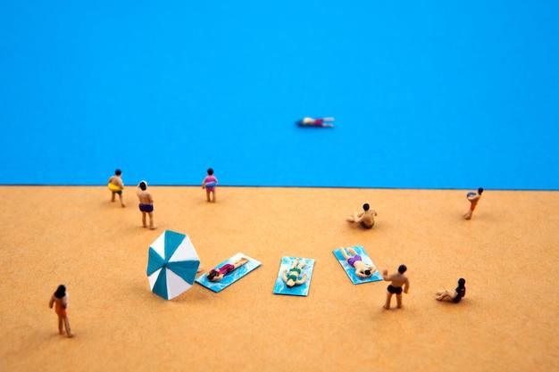 Persone in miniatura nella spiaggia estiva Foto Premium
