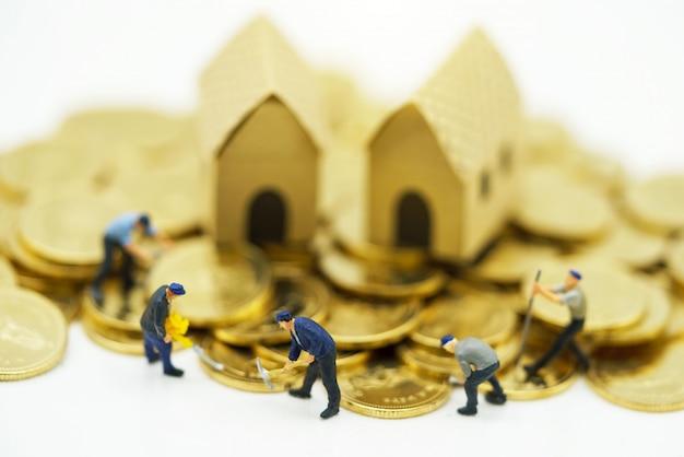 Persone in miniatura: operai che lavorano su monete d'oro con case. Foto Premium