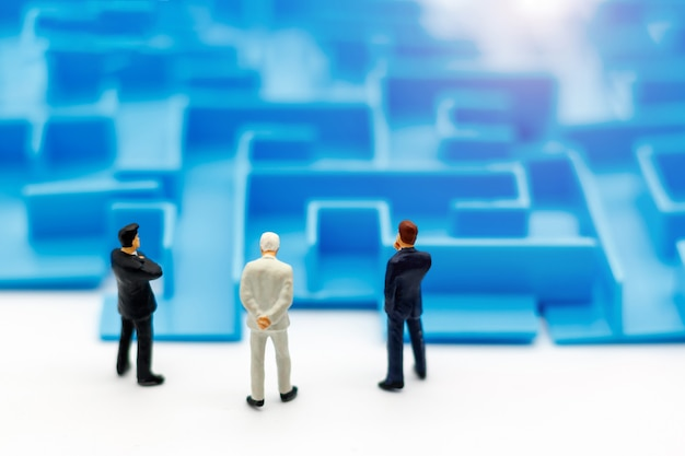 Persone in miniatura: uomo d'affari in piedi all'inizio del labirinto. Foto Premium