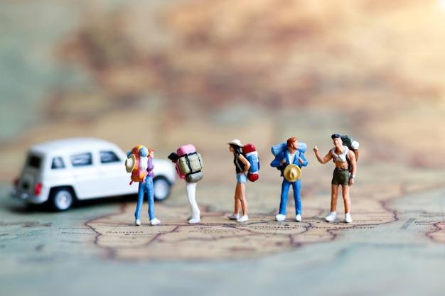 Persone in miniatura: viaggiatore con zaino in piedi sulla mappa vintage. Foto Premium