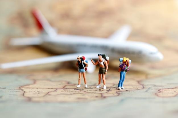 Persone in miniatura, zaino in spalla con aereo. Foto Premium