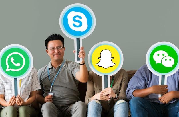 Persone in possesso di icone di marchi digitali Foto Gratuite