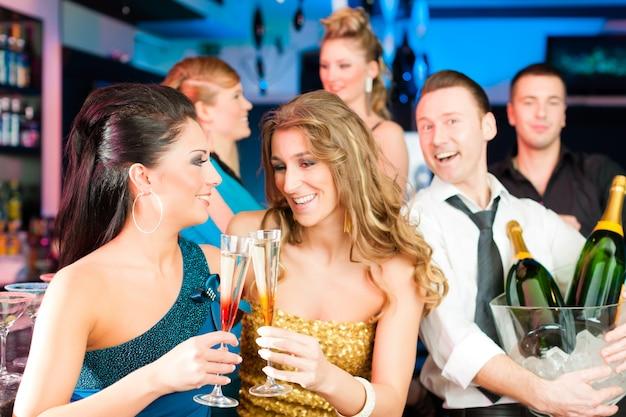 Persone nel club o al bar bevendo champagne Foto Premium