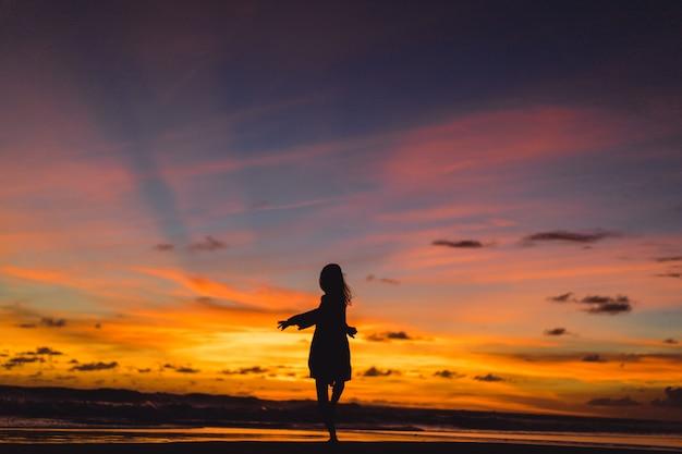 Persone sulla spiaggia al tramonto. la ragazza sta saltando sullo sfondo del tramonto. Foto Gratuite