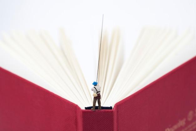 Pesca in miniatura dell'uomo su un libro Foto Premium