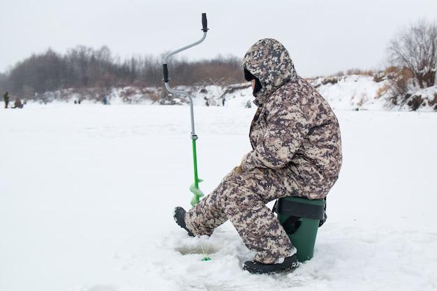 Pesca invernale. pescatore del ghiaccio che pesca in inverno sul fiume. Foto Premium