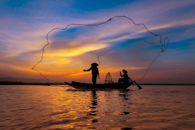 Pescatore asiatico con la sua barca di legno nel fiume della natura al mattino presto prima dell'alba Foto Premium