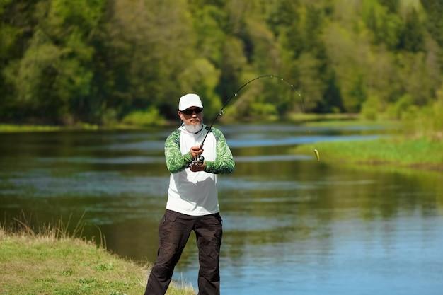 Pescatore cercando di fare un lancio perfetto lanciare esca Foto Premium