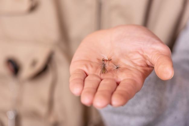 Pescatore che mostra la palma della mano del gancio della mosca di pesca. Foto Premium
