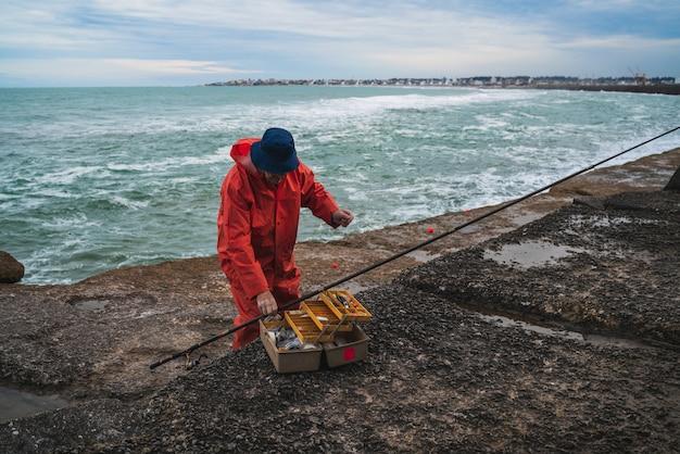 Pescatore con scatola per attrezzatura da pesca. Foto Gratuite