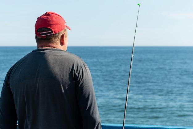 Pescatore pesca dal molo Foto Premium