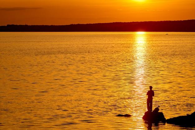 Pescatore sul molo al momento del tramonto Foto Premium