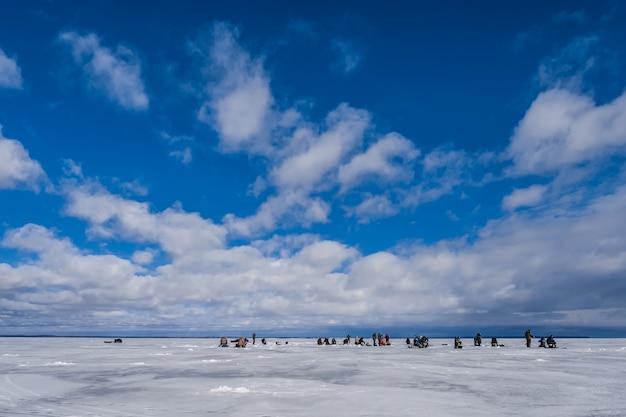 Pescatori che pescano pesce in inverno sul ghiaccio un giorno Foto Premium