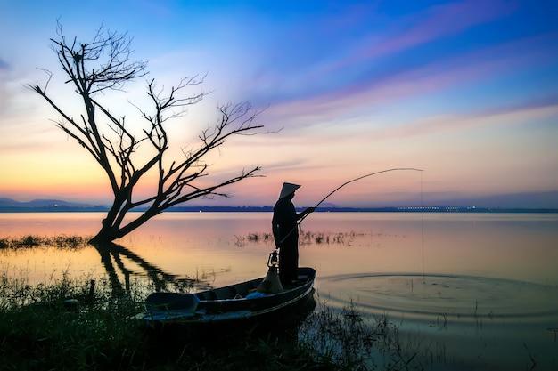Pescatori la canna da pesca con l'amo sta andando a pescare al mattino presto con il boa di legno Foto Premium