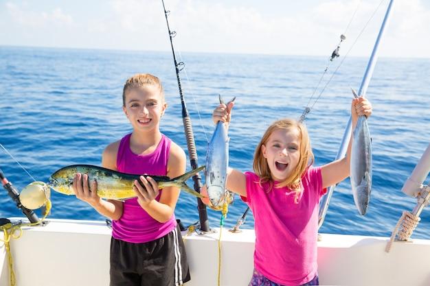 Pescatrici di tonno felice scherzano le ragazze con i pesci catturati Foto Premium