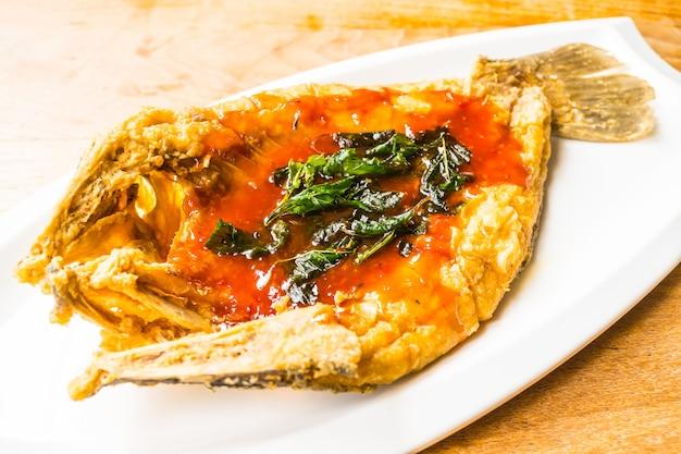 Pesce branzino fritto in piatto bianco con salsa piccante e dolce Foto Gratuite