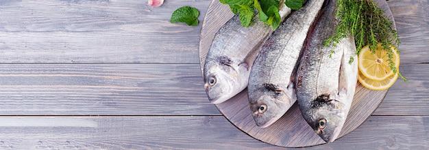 Pesce crudo di dorado con le erbe verdi che cucina sul tagliere. banner. vista dall'alto Foto Premium