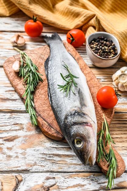 Pesce crudo fresco del branzino con le erbe sulla tavola bianca. Foto Premium