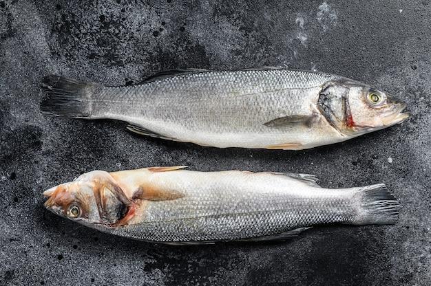 Pesce crudo fresco del branzino sulla tavola nera. Foto Premium