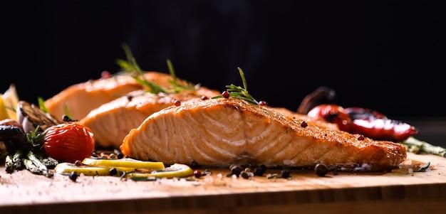 Pesce di color salmone arrostito e varie verdure sulla tavola di legno sul nero Foto Premium