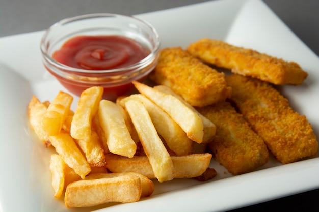 Pesce e patate fritte del primo piano con le patate fritte - alimento non sano, backgrpound grigio. Foto Premium