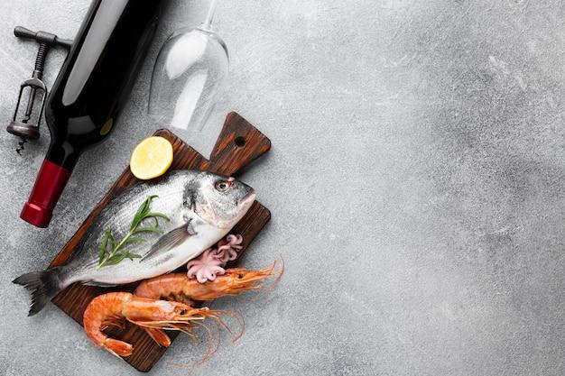 Pesce fresco ad alto angolo con vino Foto Gratuite
