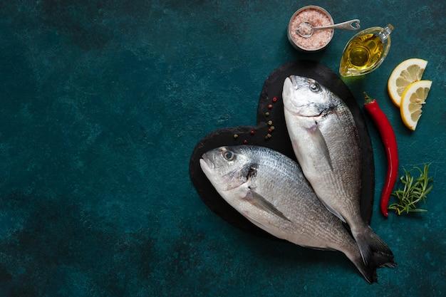 Pesce fresco di dorado, spezie e olio d'oliva sul tagliere di pietra sul tavolo scuro. vista dall'alto, copia spazio. Foto Premium