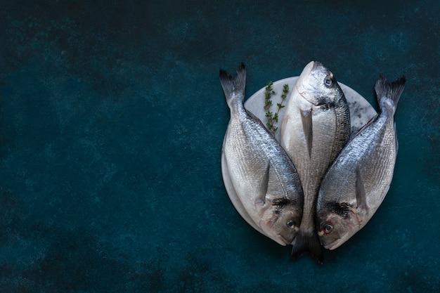 Pesce fresco di dorado sul tagliere di pietra sulla tavola blu. vista dall'alto, copia spazio. Foto Premium