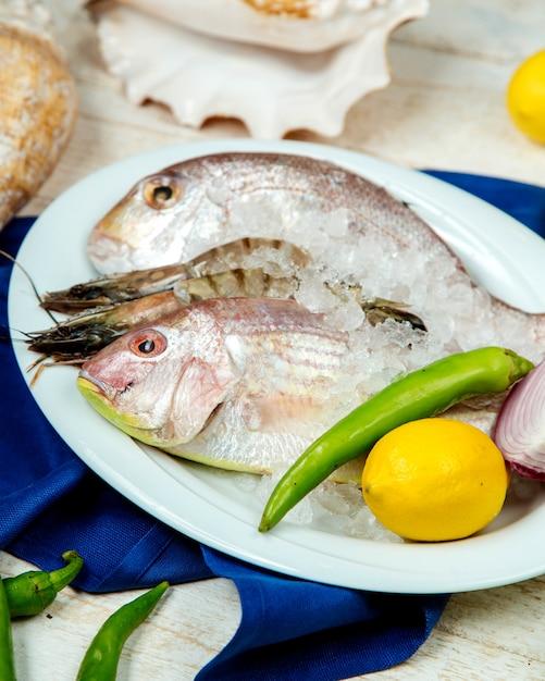 Pesce fresco e gamberi in ghiaccio guarnito con pepe, limone e cipolla Foto Gratuite