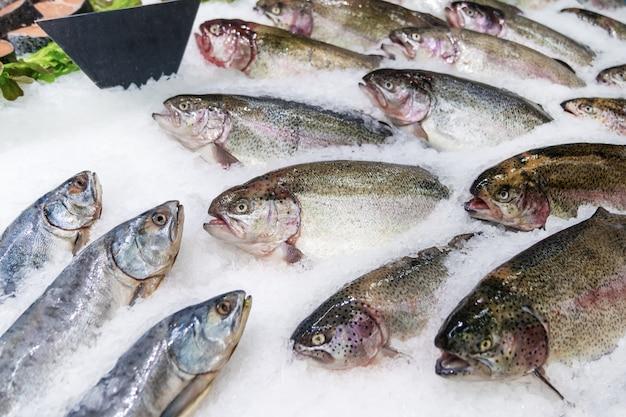 Pesce fresco su ghiaccio decorato per la vendita al mercato, salmone rosa Foto Premium